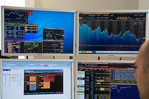 City hedge fund manager in front of financial charts on computer screens London England UK